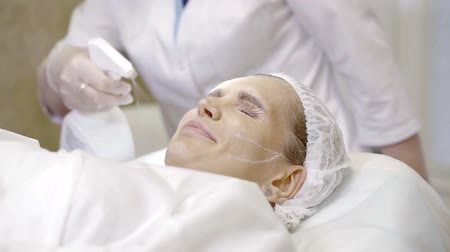 mezoterapia : patient woman is lying in a table in an operational room, nurse is spraying liquid on her face