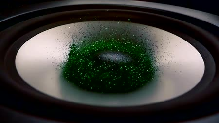 cercar : bright green sequins are lying on a surface of speaker and flying during music sound