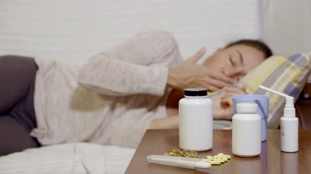 to take : brunette woman is lying on a couch, feeling bad, looking on a table with pills, taking thermometer