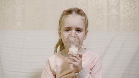 lung : child girl is sick and curing herself by modern nebulizer at home, she is bringing to face and breathing