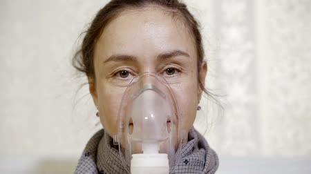 elderly care : middle-aged sick woman is inhaling and exhaling stream with medication through nebulizer, sitting in a light room