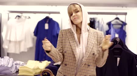 különc : extravagant adult blonde is dancing in a trading hall of clothing shop, trying on a plaid jacket, having fun