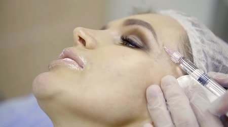 mezoterapia : face of beautiful woman on a procedure of mesotherapy, doctor is piercing skin around eyes with a syringe Wideo