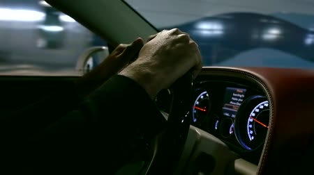 odometer : Close up shot of a mans hands on steering wheel in moving car.