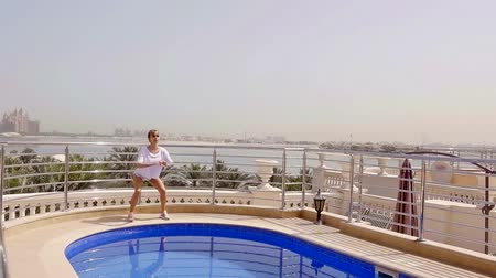 squatting : pretty woman is doing workouts in morning standing near private swimming pool in house wirth city landscape