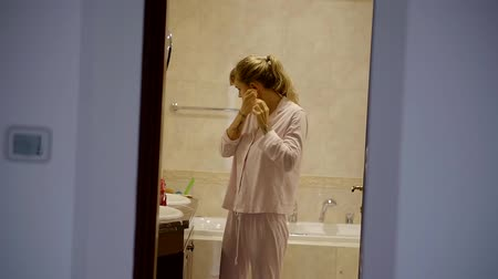 get out : pretty young woman is taking out her earrings in a bathroom and getting out, ready for bed in her flat in night