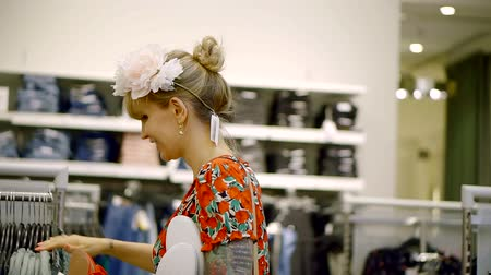 výstřední : extravagant woman is watching and choosing accessories in a shop, trying a floral wreath on her head