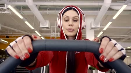 video reel : The girl athlete in a red jacket is engaged in cardio training in a sports club. Listens to your favorite music with large headphones. Stock Footage