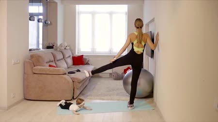 формы сердца : Exercise the muscles of the buttocks at home exercise legs aside. a young mother with a child plays and trains in her living room.