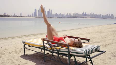 crouch : sexy woman doing mahi foot lying on a deckchair during a vacation in the sun