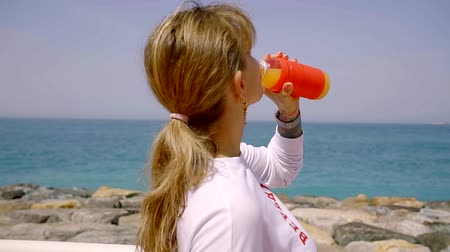 crouch : A young sportswoman drinks water from a cup during a break during a beach session Stock Footage