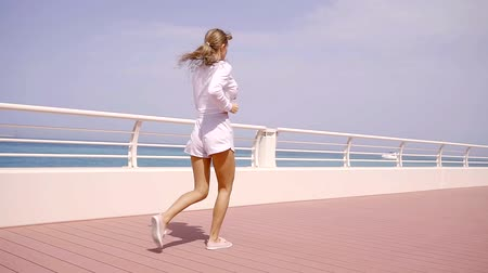 reclináveis : Young athlete kneads the muscles of the body while jogging along the coastal territory Vídeos