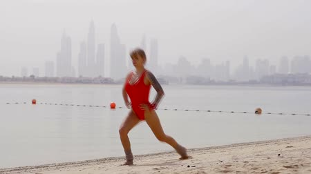 crouch : young woman jogging in a swimsuit in the summer time on the beach