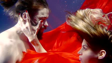 mar vermelho : close up. cute couple deep underwater in red cloth hugging like a fairy tale Vídeos