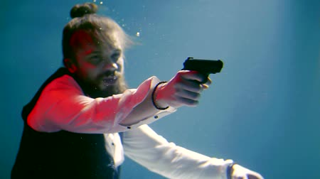 bandido : Bearded man in a shirt and vest to aim a gun under water Vídeos