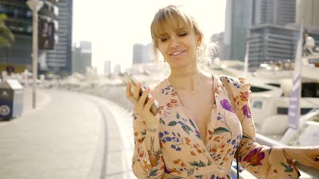 blondýnka : Happy and cheeful woman walking across the city and talking on the phone.