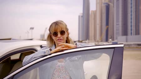 домик : Close up shot of a beautiful blonde woman posing by the luxury car on the beach.