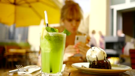 rejoice : contemporary girl is taking pictures of her food in a cafe and rejoicing, blurred view, green juice cocktail is in foreground