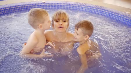 джакузи : two little sons are kissing in cheek their mother, bathing in a pool with hydromassage bath Стоковые видеозаписи