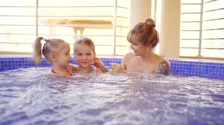 calor : mother with her two little daughters is warming in pool with hot and seething water Vídeos
