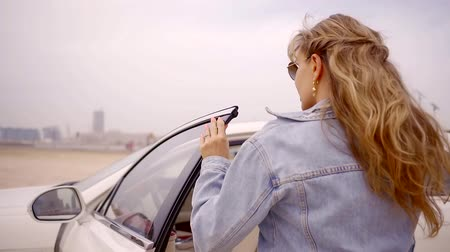 выход : pretty woman with wavy blonde hair is exiting from her white car and looking in camera in summer day