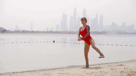 squatting : girl is wearing bright red swimsuit is doing physical exercise, rising legs and squatting on a beach in sunny morning