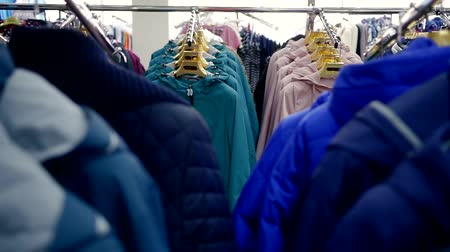 sem camisa : close shot at the ranks with clothes, a lot of different jackets are on the hangers in the store Stock Footage