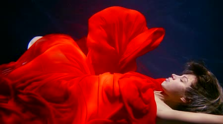 lem : a young woman swims under the water in a red dress, she looks like a fairy-tale character Dostupné videozáznamy