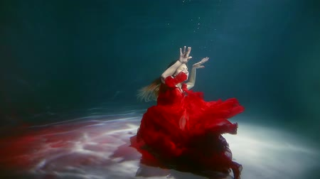 lem : a young woman dressed in a red dress is like a flower, a lady raises her arms up while she is under water Dostupné videozáznamy