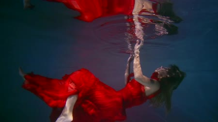 tmavé vlasy : a woman dressed in a red dress swims under the water, her body reflects on the edge of the water