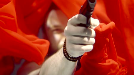 lem : The man directs the gun to the distance, his hand thrusts through the red cloth