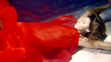 mar vermelho : a young woman dressed in a scarlet dress is like a mermaid floating on the seabed
