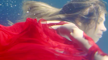 lem : close shot on scarlet cloth, young woman appears because of her during swimming