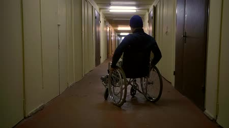 wheelchair ramp : Shot from behind of a man on a wheelchair in a hospital corridor.