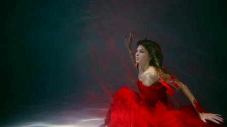 afloat : lonely sensual woman in silk red dress is sitting inside water in bottom of large aquarium and stretching hands up Stock Footage