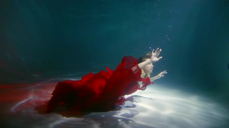 marad : alone calm young woman in red-blooded dress is floating underwater near bottom in rays of sunshine Stock mozgókép