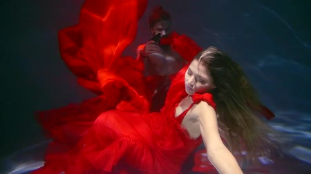 afloat : underwater shot of two people in a pool, woman is wearing red long dress is at gunpoint of anger man