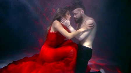 afloat : underwater shot of sad young man is trying to embrace pretty woman in red dress, but she is leaving him and swimming away Stock Footage