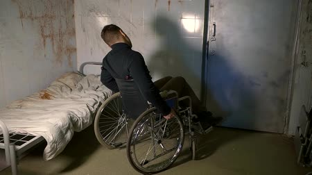 inwalida : male disabled wheelchair user is whirling in a hospital room with dirty bloody walls and linen on bed, bad conditions