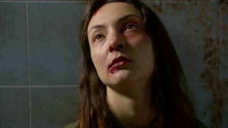 yara : battered young woman with bloody wound and fresh bruise under eye is sitting leaned on a dirty wall in bathroom