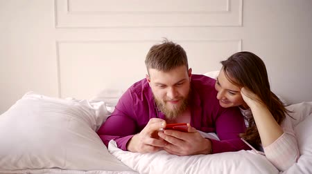 darling : a loving couple lies on a bed, a smart holding a smartphone in his hands, his wife looks at the screen