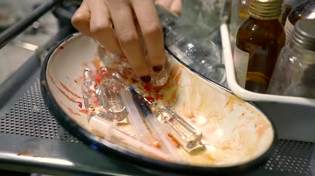 addicted : a close shot at the womans hand, who digs in a bowl with medical instruments, the person takes out the medicine Stock Footage