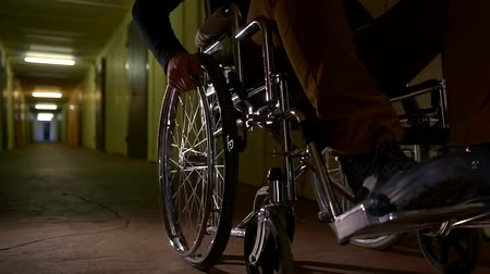 amputee : close up shot of a wheelchair, a man twists the wheels in order to move around the hospital hall