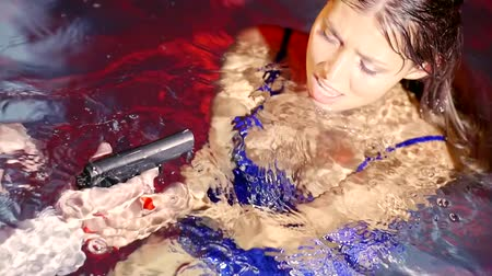 guns : Close up shot of a woman and her man with a gun in the pool. Stock Footage