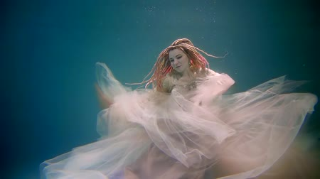 lem : a young woman shows up at the hem of a dress that flutters under the water, the atya in which she is dressed, the lady seems mystical and frightening with dreadlocks on her head Dostupné videozáznamy