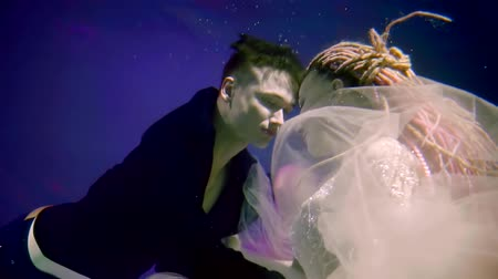 lem : a young man swims to a woman with dreadlocks, which floats under water in a gorgeous dress