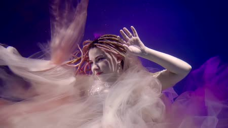 ninfa : a mystical woman is on the seabed and elegantly moves her hands, her hair is braided in dreadlocks