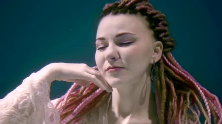 ninfa : a magical woman is under water and touches her face, she has dreadlocks and accessories