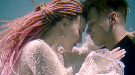 intim : portrait of a couple in love who embrace under water, young husband and wife kissing under water Stock Footage