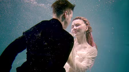 intim : actress and actor hugging underwater during the filming, the lady hugs her husband and smiles Stock Footage